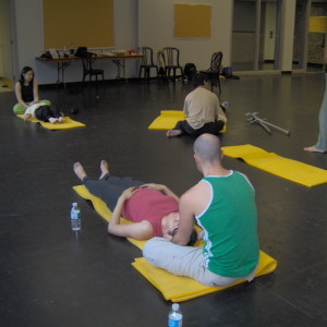 Artists work in pairs on floor mats, taking turns exchanging roles during exercises; Fides observes.