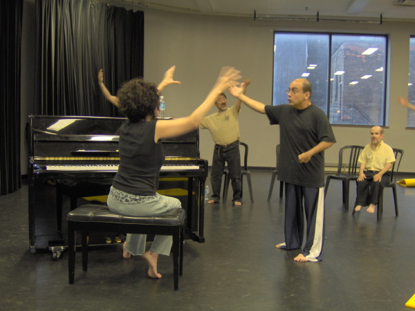 Fides at piano faces Paul, arms raised to release energy; Kaz mirrors arm movements behind.