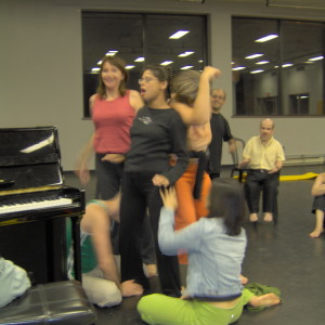Four artists cluster around Michelle at the piano making body contact with her while she vocalizes with Fides.