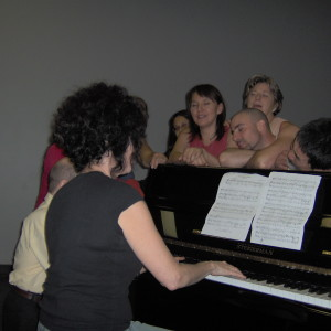 Group clusters around Fides at keyboard while she plays; Kaz and Anthony make contact with vibrations resting their heads on piano lid.