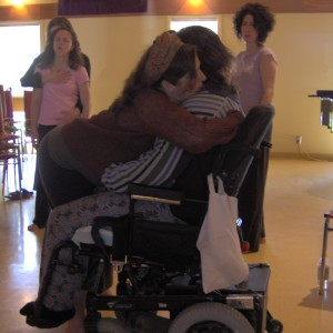 Tracy faces artist in wheelchair enfolds him in her arms; Fides and others watch; Regina Workshop for CP Salon.
