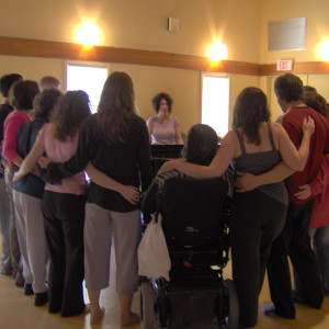 Participants stand arms linked in a semi-circle around Fides at grand piano, singing together, Regina Workshop CP Salon.