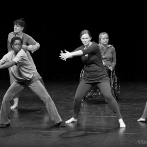 Five ensemble members repeat a circular scooping motion with arms and clasped hands; Melissa behind them in wheelchair.