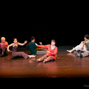 Ensemble members seated on the floor legs outstretched, continue funky arm motions while dragging themselves across the floor