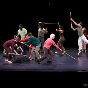 Ensemble members prance and play using their bamboo poles, stage right four of them huddle around wheelchair with poles