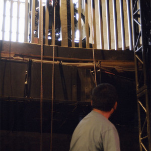 Kaz in theatre pit looks up at Melissa leaning over mezzanine in wheelchair, ropes dangle from above
