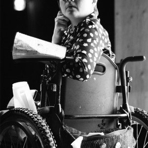 Melissa with notebook and cell phone in wheelchair