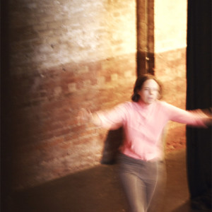 Blurred image Helen runs forward arms outstretched, in theatre pit
