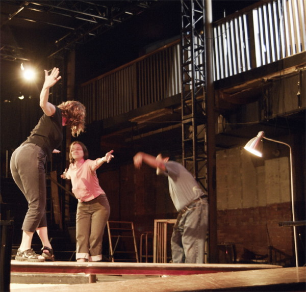 Rose, Helen, Kaz, bow to each other with great flourish, on platform in theatre pit.