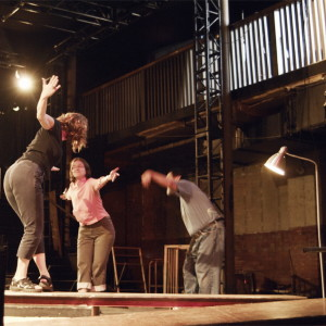 Rose, Helen, Kaz, bow to each other with great flourish, on platform in theatre pit