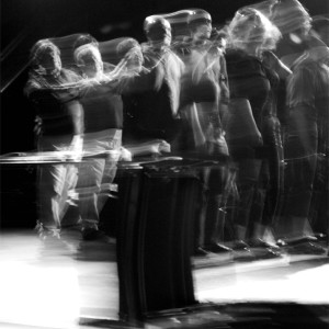Blurred time lapse image of audience and performers moving forward in a line