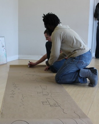 Pete, Ali on hands and knees, create storyboard with markers on long roll of paper.