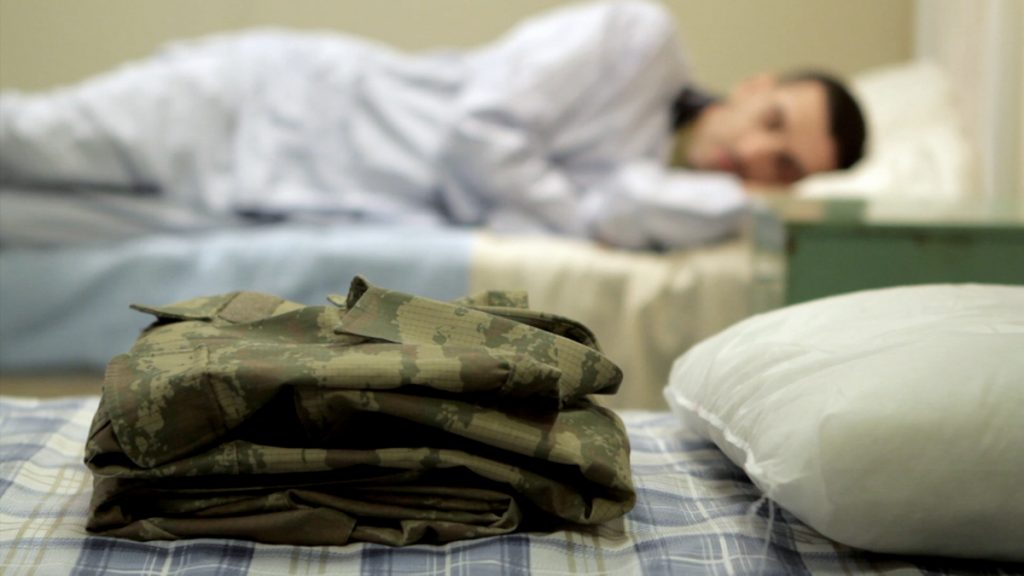 A soldier lies on a hospital cot staring at a folded army uniform