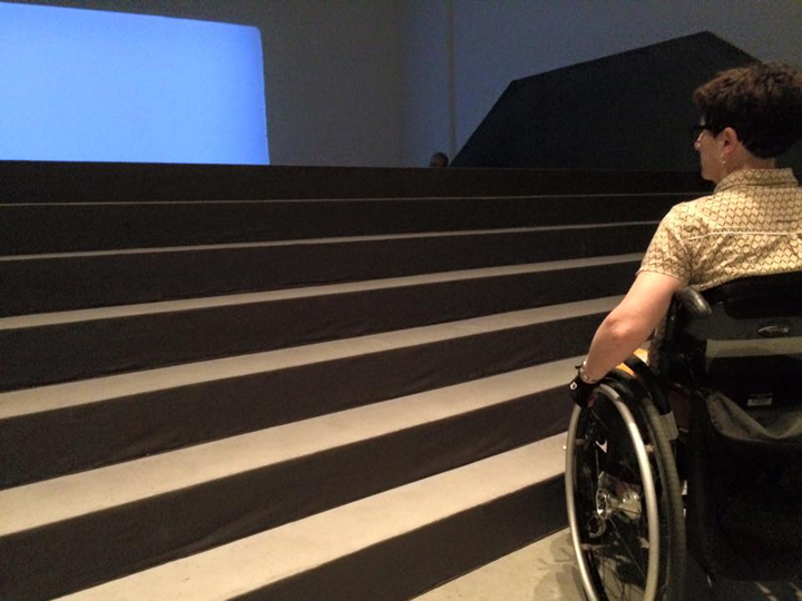 A woman using a wheelchair faces several steps between her and the projection screen within an installation